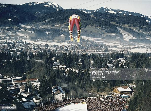 Ein Skispringer im roten Skianzug fliegt im VStil von der Schattenbergschanze Unter ihm liegen der Auslauf der Schanze und die Zuschauertribünen im...