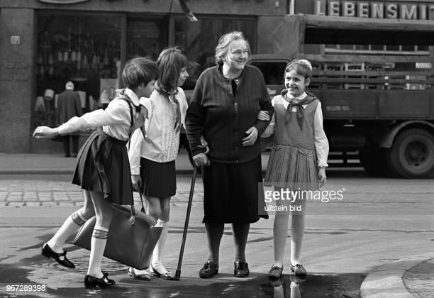 Ein sogenannter Timurtrupp begleitet eine hilfsbedürftige Rentnerin über eine Straße in Dresden aufgenommen 1968 Selbstlose Hilfe für Bedürftige...