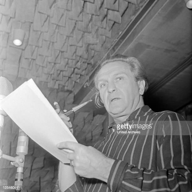 Ein Sprecher einer NDR Hörspielproduktion mit einer Zigarrenspitze, Deutschland 1950er Jahre.