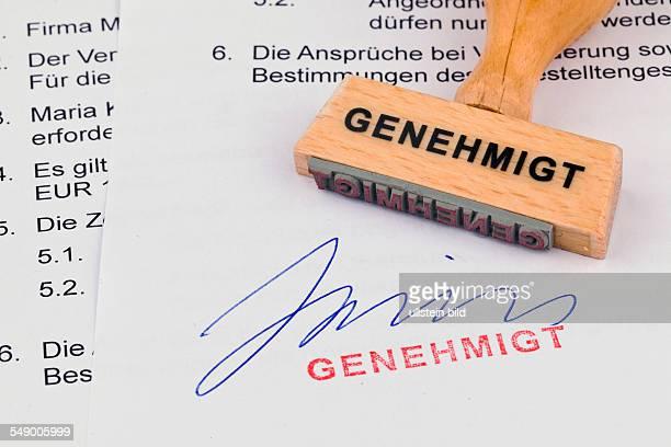 Ein Stempel aus Holz liegt auf einem Dokument Aufschrift Genehmigt