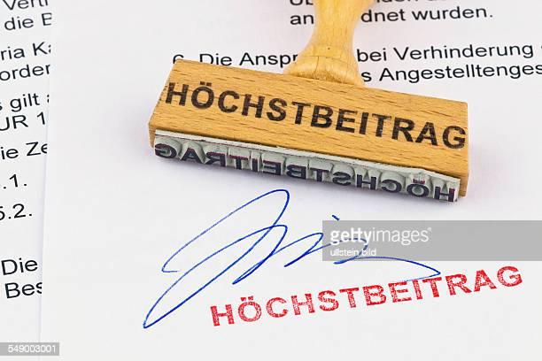 Ein Stempel aus Holz liegt auf einem Dokument Aufschrift Höchstbeitrag