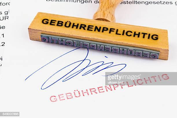 Ein Stempel aus Holz liegt auf einem Dokument Aufschrift Gebührenpflichtig
