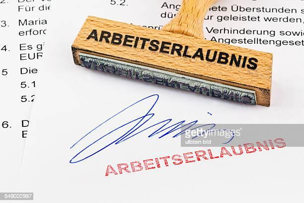Ein Stempel aus Holz liegt auf einem Dokument Aufschrift Arbeitserlaubnis
