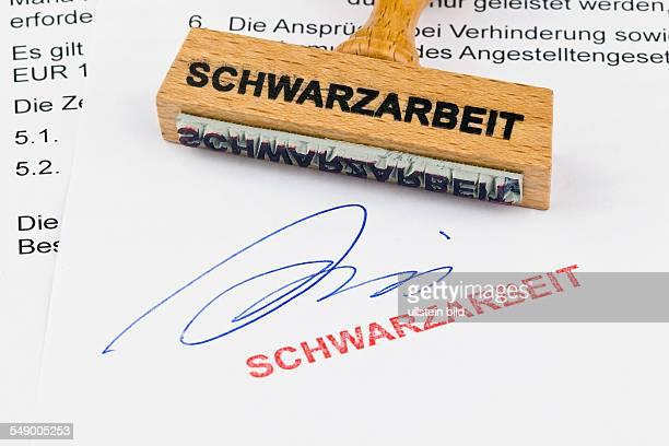 Ein Stempel aus Holz liegt auf einem Dokument Aufschrift Schwarzarbeit