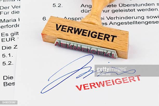 Ein Stempel aus Holz liegt auf einem Dokument Aufschrift Verweigert