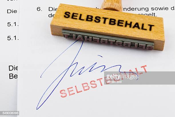 Ein Stempel aus Holz liegt auf einem Dokument Deutsche Aufschrift Selbstbehalt