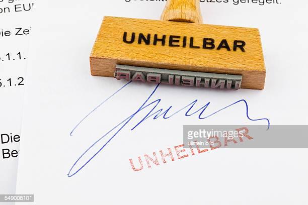 Ein Stempel aus Holz liegt auf einem Dokument Deutsche Aufschrift Unheilbar