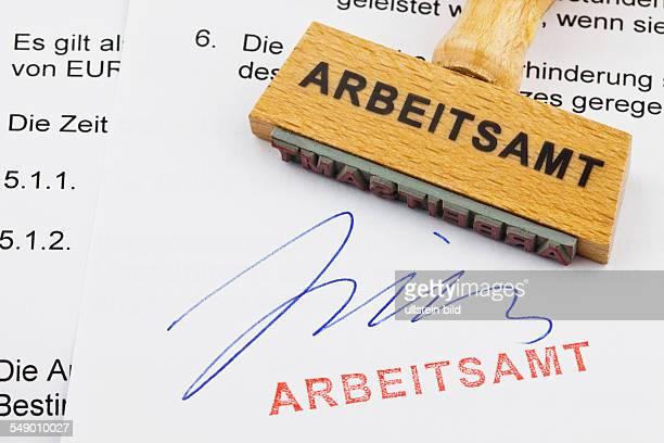 Ein Stempel aus Holz liegt auf einem Dokument Deutsche Aufschrift Arbeitsamt