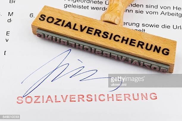 Ein Stempel aus Holz liegt auf einem Dokument Deutsche Aufschrift Sozialversicherung