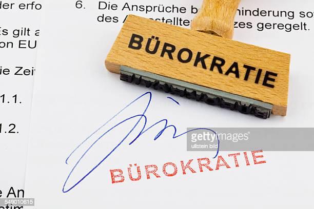Ein Stempel aus Holz liegt auf einem Dokument Deutsche Aufschrift Bürokratie