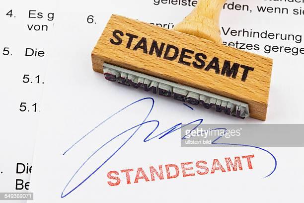 Ein Stempel aus Holz liegt auf einem Dokument Deutsche Aufschrift Standesamt