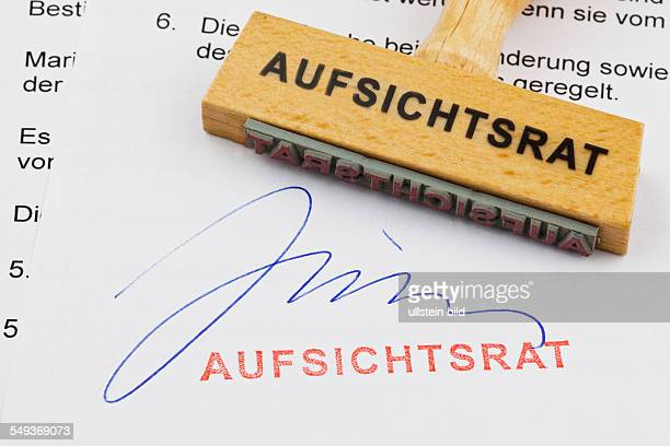 Ein Stempel aus Holz liegt auf einem Dokument Deutsche Aufschrift Aufsichtsrat