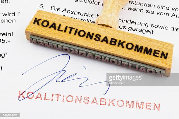 Ein Stempel aus Holz liegt auf einem Dokument Deutsche Aufschrift Koalitionsabkommen