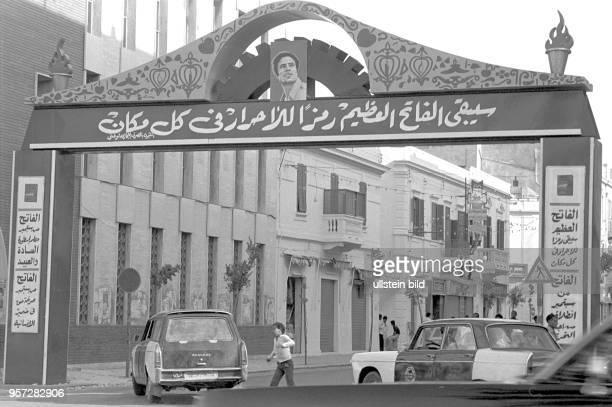 Ein stilisiertes Tor mit arabischer Schrift und dem Porträs des libyschen Revolutionsführer Oberst Muammar Abu Minyar alGaddafi überspannt eine...