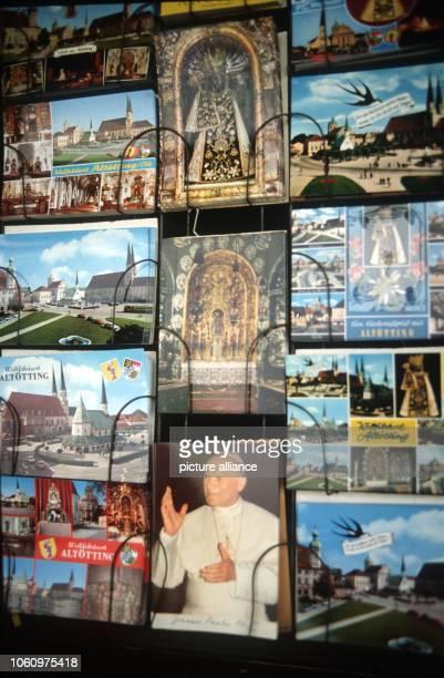 Ein Ständer mit verschiedenen Ansichtskartenkarten unter anderem eine Postkarte auf der ein Porträt des Papstes Johannes Paul II abgebildet ist...