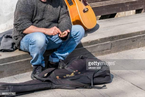 Ein Strassenmusiker zählt seine Einnahmen Überleben als Künstler