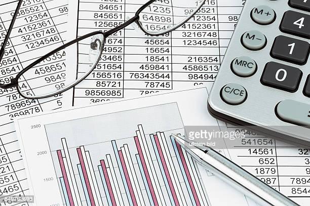 Ein Taschenrechner liegt auf den Zahlen einer Bilanz uns Statistik Symbolphoto für Umsatz Gewinn und Kosten
