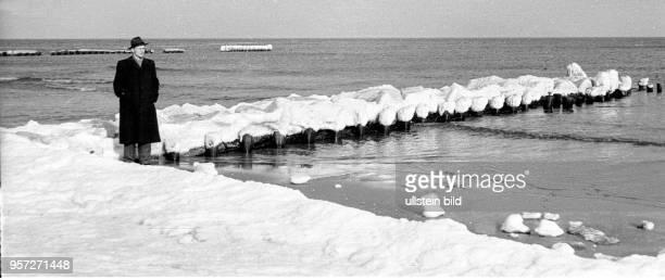 Ein Tourist mit Hut und Mantel vor einer vereisten Buhne am Strand vom Ostseebad Koserow auf der Insel Usedom im Winter 1957 Foto Reinhard Kaufhold...