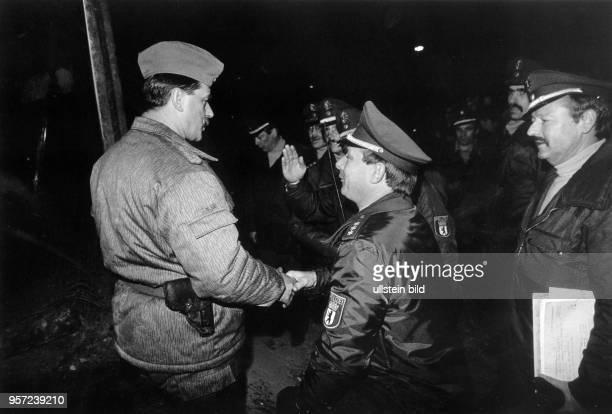 Ein uniformierte DDRGrenzer reicht einem Westberliner Polizisten an der Berliner Mauer am Potsdamer Platz die Hand aufgenommen am Die Grenzöffnung...