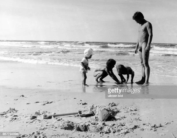 Ein Vater mit seinen Kindern am FKKStrand bei Nonnewitz auf der Insel Rügen aufgenommen im Sommer 1975 Ein Sommerurlaub an der Ostsee gehörte zu den...