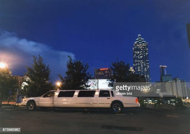 Ein weiße Stretchlimousine vor der nächtlichen Skyline Atlantas erleuchtete Hochhäuser / Wolkenkratzer und Straßenlaternen glitzern am dunklen Himmel...