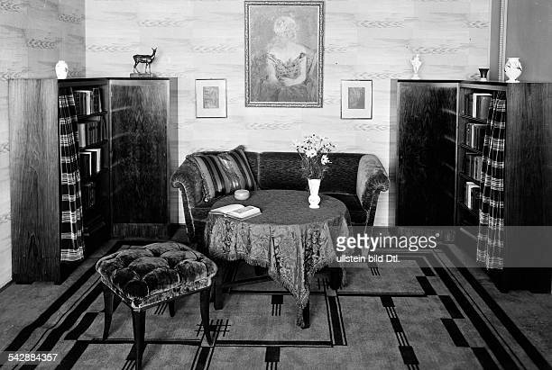 Ein Wohnzimmer mit zwei Bücherschränkeneinem Sofa einem Tisch mit einerTischdecke einem gepolsterten HockerBildern an der Wand und einem Teppich...