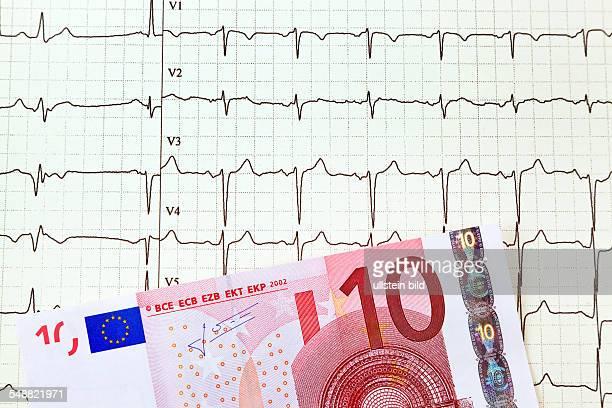 Ein Zehneuroschein liegt auf einer EKG Kurve Arztkosten und Zuzahlung
