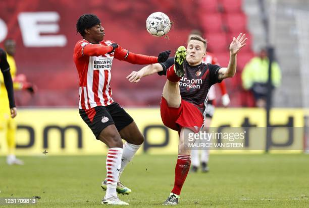 Eindhoven English forward Noni Madueke fights for the ball against Feyenoord Dutch midfielder Jens Toornstra during the Dutch Eredivisie match...