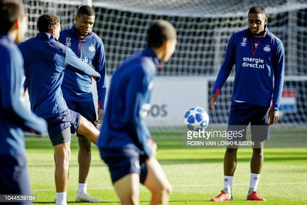 PSV Eindhoven's Dutch forward Denzel Dumfries and Dutch midfielder Pablo Rosario eye a ball during a training session in Eindhoven on October 2 2018...