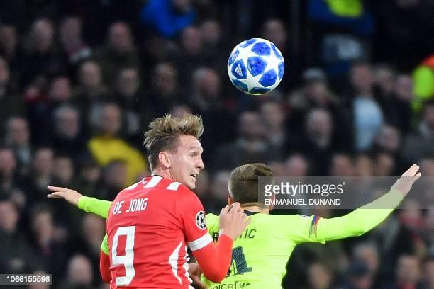 Eindhoven's Dutch forward Luuk De Jong and Barcelona's Croatian midfielder Ivan Rakitic during the UEFA Champions League football match between PSV...