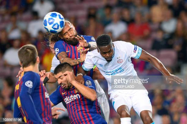 PSV Eindhoven's French defender Nicolas IsimatMirin jumps for the ball with Barcelona's Chilean midfielder Arturo Vidal and Barcelona's Uruguayan...