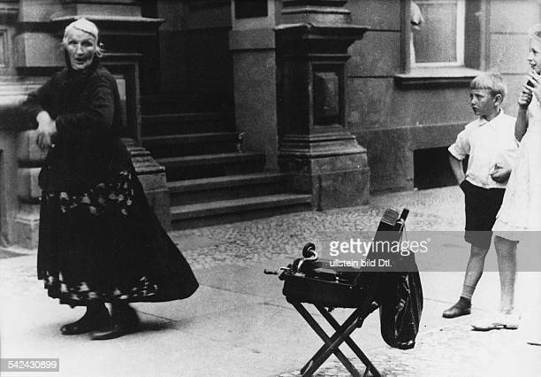 Eine alte Frau verdient sich ihren Lebensunterhalt indem sie zu Musik aus einem Gramophon auf dem Gehweg tanztum 1950