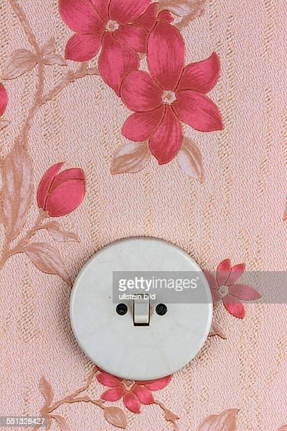 Eine alte Tapete mit Lichtschalter Symbolfoto für Erneuerung und renovieren