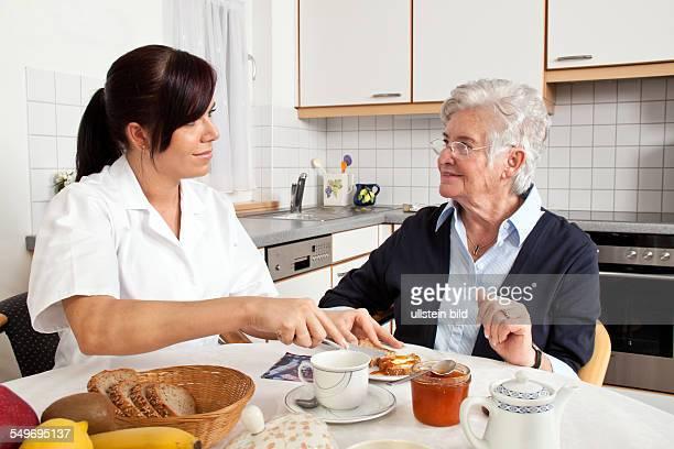 Eine Altenpflegerin hilft Seniorin beim Frühstück