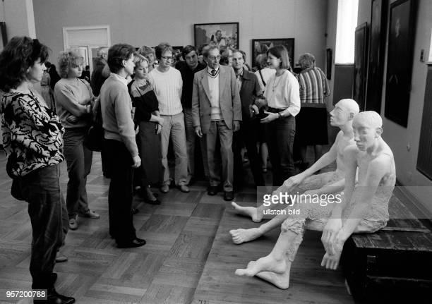 Eine Besuchergruppe betrachtet auf der X Kunstausstellung der DDR in Dresden die Plastik 'Sitzende' der Bildhauerin Thea Richter Die Kunstausstellung...