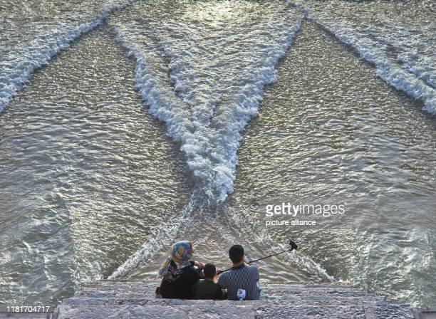 Eine Familie sitzt an der Khadju-Bru_cke über den Zayandeh Rud Fluss in der iranischen Stadt Isfahan, aufgenommen am . Die zweistöckigen Brücke mit...