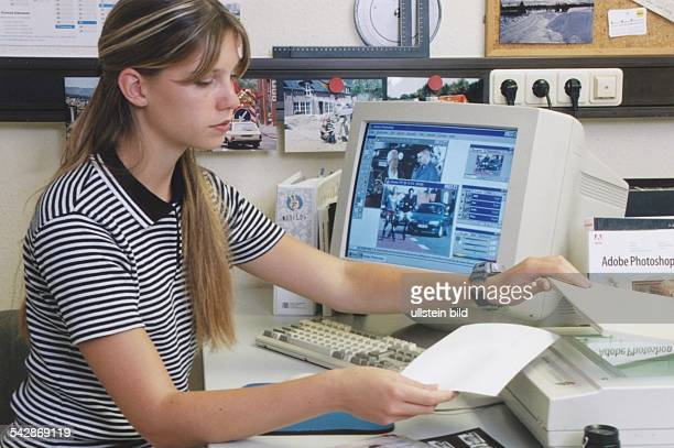 Eine Fotomedienlaborantin legt eine Vorlage in einen Scanner ein Links an ihrem Arbeitsplatz der Computer an dem sie die Fotos bearbeiten kann...