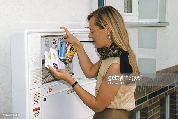 Eine Frau entnimmt ihrem Briefkasten Werbeprospekte Aufgenommen um 1998
