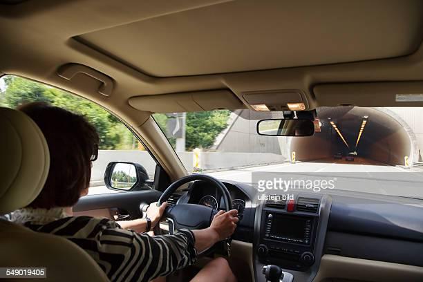 Eine Frau fährt mit ihrem Auto in einen Tunnel