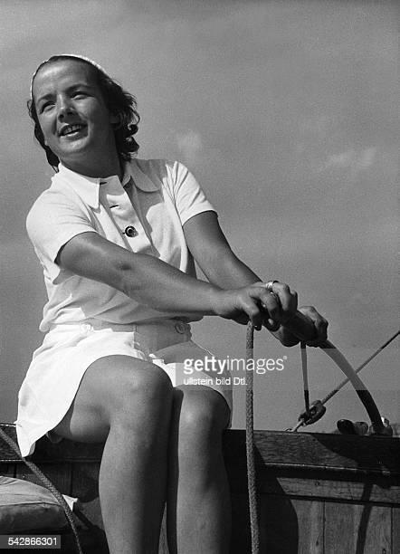 Eine Frau hält die Ruderpinne eines Bootes1956
