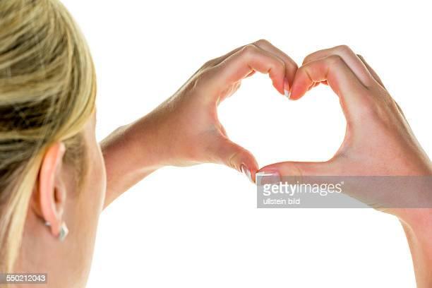Eine Frau hält ihre Hände in der Form eines Herzen Symbolfoto für Liebe
