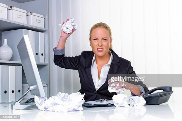 Eine Frau im Büro wirft mit zusammengeknülltem Papier Ärger Stress und Frust am Arbeitsplatz