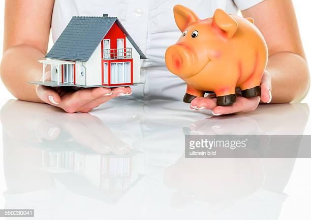 Eine Frau mit einem Haus und einem Sparschwein Die richtige Finanzierung für den Hauskauf
