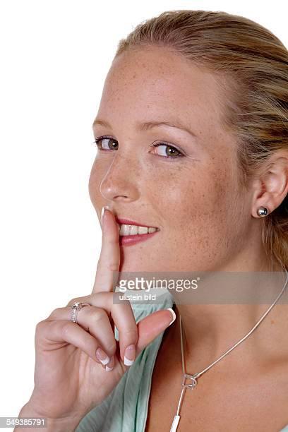 Eine Frau mit Finger am Mund. Symbolfoto für Verschwiegenheit und Geheimnisse