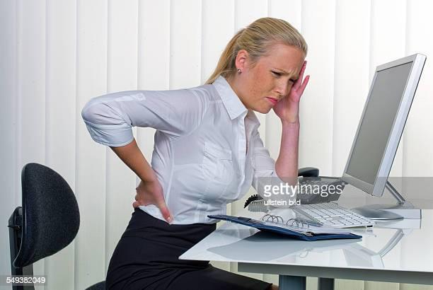 Eine Frau mit Rückenschmerzen vom langen Sitzen im Büro Gesundheit und Vorsorge am Arbeitsplatz