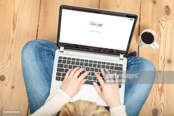 Eine Frau sitzt auf dem Boden und ist mit ihrem Laptop auf der Startseite von Google