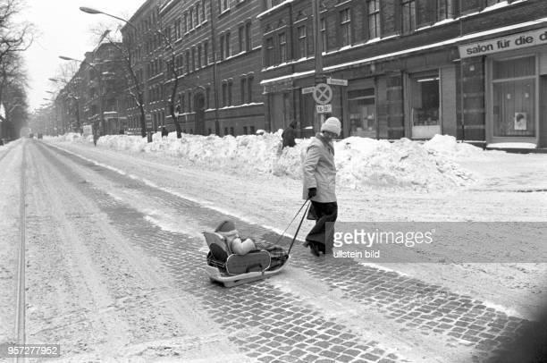 Eine Frau zieht einen Schlitten mit einem Kind über die glatte Schönhauser Allee in Berlin Prenzlauer Berg undatiertes Foto vom Februar 1979 Extreme...
