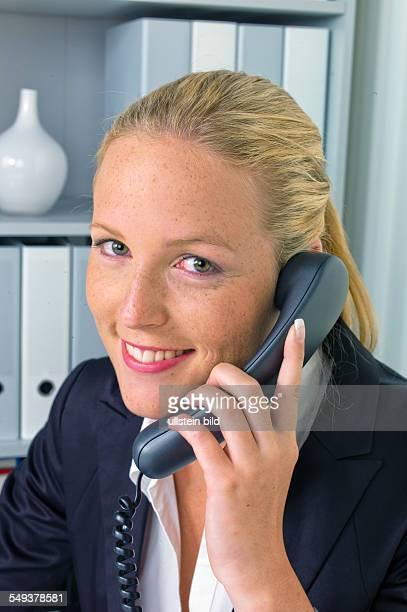 Eine freundliche Frau telefoniert an ihrem Schreibtisch im Büro