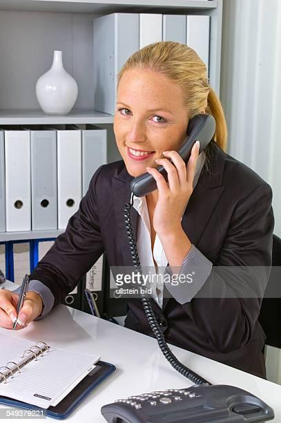 Eine freundliche Frau telefoniert an ihrem Schreibtisch im Büro und notiert Termine im Kalender