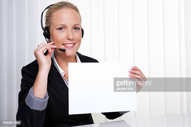 Eine freundliche junge Frau mit Headset im Kundendienst telefoniert mit einem Kunden Freundliche Hotline Mitarbeiterin